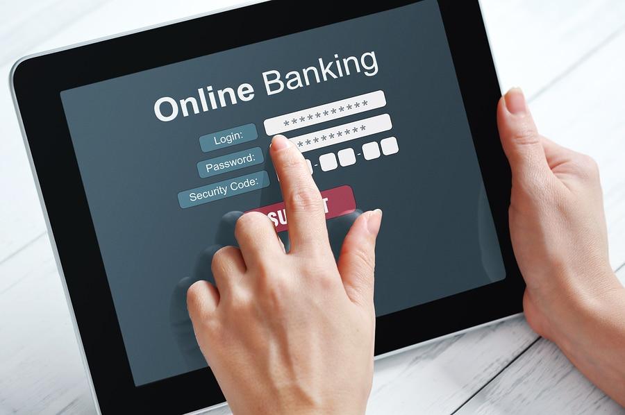 Mains d'une femme  sur un appareil à écran tactile d'un service bancaire . Accéder à son compte en baque  avec identifiant et mot de passe .
